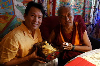Fred Cheong is offering Rinpoche a medallion smaller than a nickel with 1,000 Namgyalma mantras on it. Photo: Ven. Roger Kunsang May 4, 2013.
