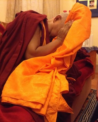 Lama Zopa Rinpoche blessing robes before they are offered to Buddha statue in Mahabodhi Temple, Bodhgaya.
