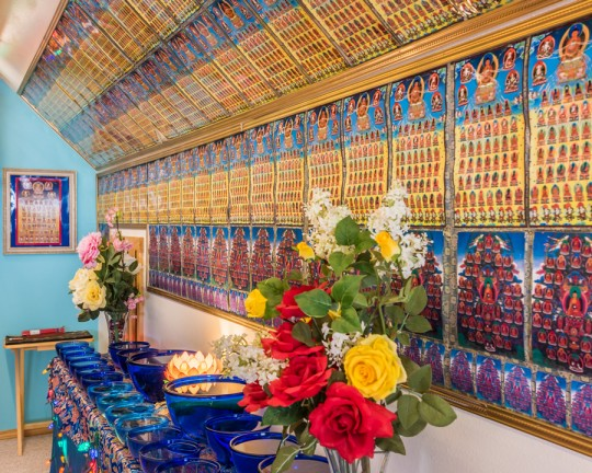 Offering and dozens of images of the 35 buddhas of confession in Lama Zopa Rinpoche's room at Buddha Amitabha Pure Land, Washington, US, June 2015. Photo by Chris Majors.