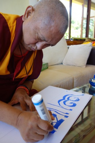 Lama Zopa Rinpoche writing mantras to go above a rabbit house located at Sera Je Monastery, India. Photo by Ven. Roger Kunsang, December, 2013.