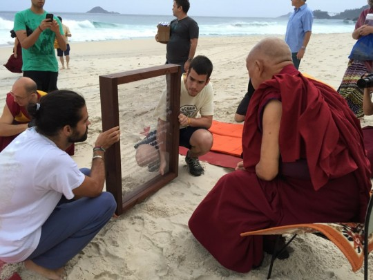 Lama Zopa Rinpoche checking the Namgyalma mantra on the newly made board for blessing beings in the ocean, Rio de Janeiro, Brazil, September 2015. Photo by Ven. Roger Kunsang.