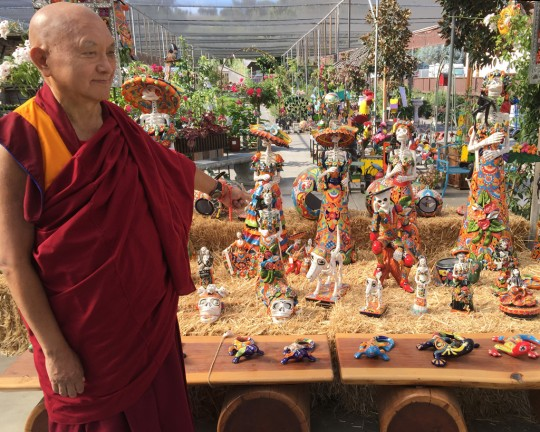 Lama Zopa Rinpoche taking interest in the Dia de los Muertos and Halloween decoration at a garden shop, California, October 2015. Photo by Ven. Roger Kunsang.