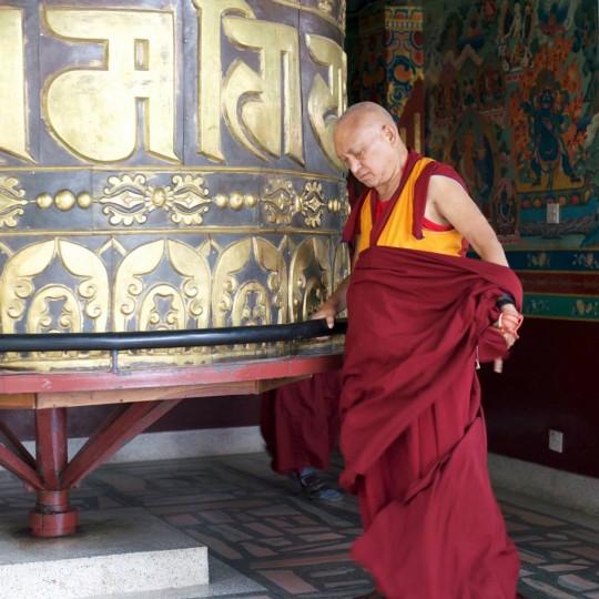 Lama Zopa Rinpoche turning the large prayer wheel at Kopan Monastery, Nepal, November 2015. Photo by Bill Kane.