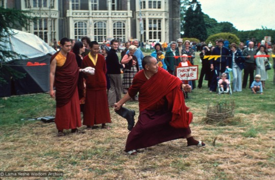 """Chris Kolb (Ngawang Chotak), Lama Yeshe and Geshe Tegchok at the Open Day festival at Manjushri Institute, England, 25th of August, 1979. Among the games staged in the gardens was the rural sport of """"wellie wanging."""" This consisted of hurling a large rubber Wellington boot as far as possible, from a standing position. Photo courtesy of Lama Yeshe Wisdom Archive."""