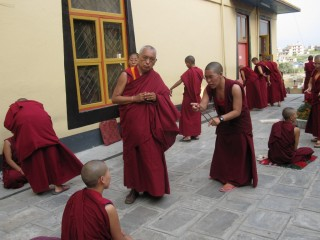 Lama Zopa Rinpoche with  monks debating.