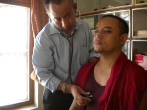Allopathic doctor giving check-up at Tashi Lhunpo Health Care Center. Photo courtesy of Tashi Lhunpo Monastery.