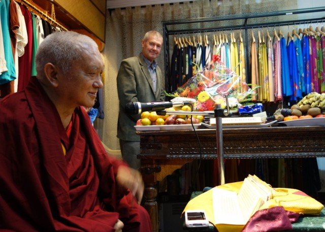 Lama Zopa Rinpoche teaching to the Nepali staff of Yak and Yeti on the good heart. Marcel Bertels in the background with some of the fine silk clothing they manufacture. December 5, 2013 Photo by Ven. Roger Kunsang.