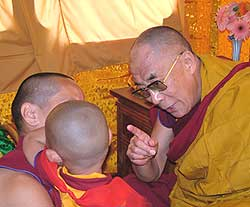 Tulku Tenzin Phuntsok Rinpoche having his hair cut by His Holiness  the Dalia Lama during the Kalachakra event. Photographer Ven Roger Kunsang