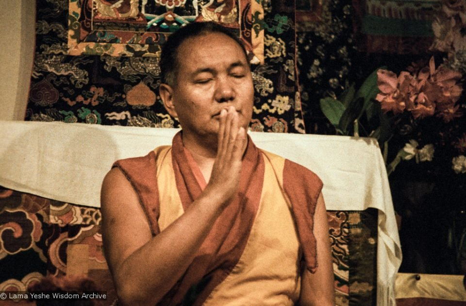 Lama Yeshe on teaching throne with eyes closed and hand raised peacefully