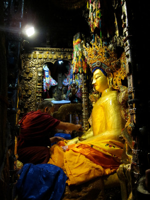 Offering of gold and robes to the holy Jowa Buddha Statue in Tibet.