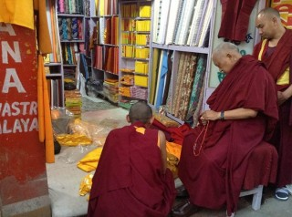 Lama Zopa Rinpoche carefully choosing the cloth that will be offered as robes for the Buddha statue at Mahabodhi Stupa.