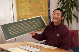 Ven. Tsering showing some of his work writing out the Prajnaparamita. Photo by Whitney Dafoe.