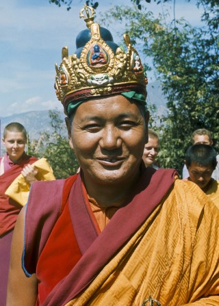 Lama Yeshe wearing a ceremonial crown of the five dhyani buddhas for the Tara statue procession, Kopan Monastery, Nepal, 1976. Behind him is Yeshe Khadro (Marie Obst) on the left and Wendy Finster and Ngawang Khyentse on the right. Photo courtesy of Lama Yeshe Wisdom Archive.