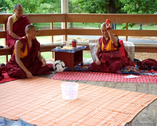 Lama Zopa Rinpoche practices tossing a small ball into a bucket during a picnic in Bendigo, Australia, October 2014. Photo by Ven. Roger Kunsang.