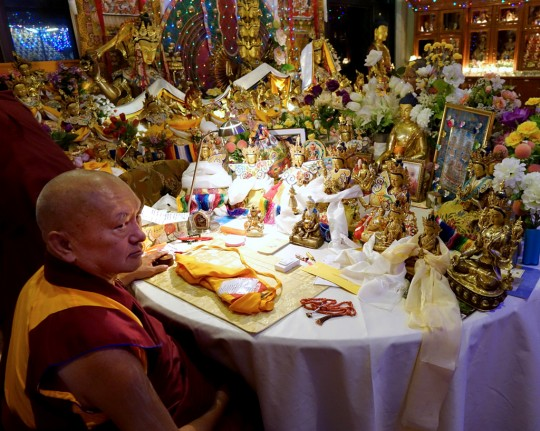 Lama Zopa Rinpoche at night in front of his work table at Kopan Monastery, which has so many statues ... another alter! Nepal, December 2014. Photo by Ven. Roger Kunsang.
