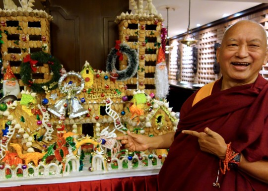 Lama Zopa Rinpoche in front of a Christmas-themed gingerbread monastery, Kopan Monastery, Nepal, December 2014. Photo by Ven. Roger Kunsang.