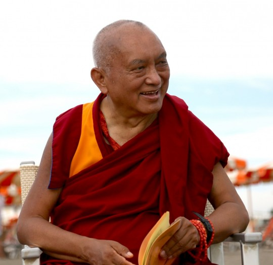 Lama Zopa Rinpoche on the beach blessing all sentient beings in the water, Italy, June 2014. Photo by Ven. Thubten Kunsang.