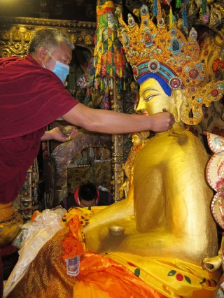 Gold is offered on Sakadawa to the precious Jowa Buddha statue in Lhasa, Tibet.