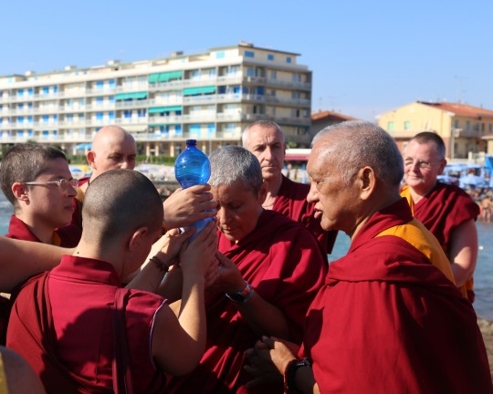 Lama Zopa Rinpoche with Sangha doing a blessing for all the sentient beings in the water, Italy, June 2014. Photo by Ven. Thubten Kunsang.