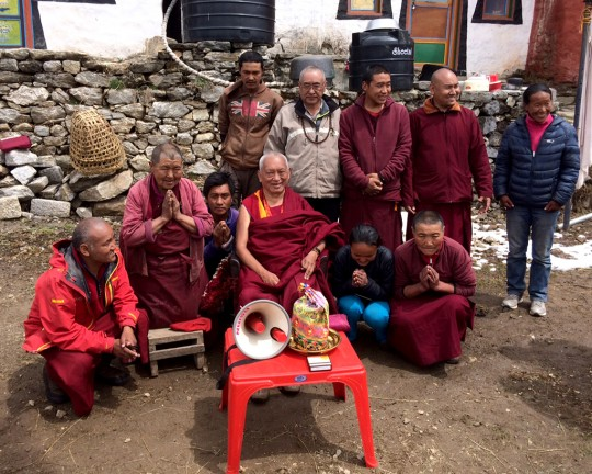 Lama Zopa Rinpoche with his sister Ani Ngawang Samten (kneeling to the left of Rinpoche) and his brother Sangay Sherpa (in the tan jacket behind Rinpoche) along with other Sherpas at Lawudo, Solu Khumbu, Nepal, April 2015. Photo by Harry Sutton.