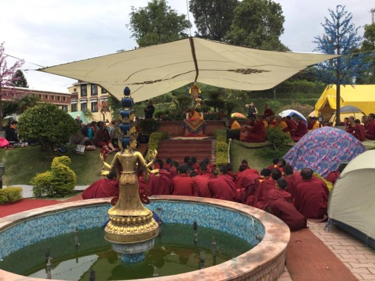 Lama Zopa Rinpoche teaches from under a tent in the enlightenment garden at Kopan Monastery, Nepal, April 27, 2015. Photo by Ven. Sarah Thresher.