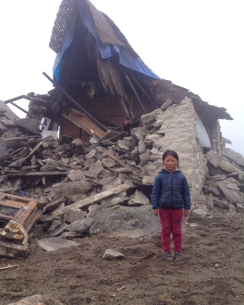 Young girl stands next to a collapsed home in Thame, Solu Khumbu district, Nepal, April 28, 2015. Photo by Jimmy Grant.