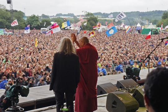 His Holiness the Dalai Lama, along with Patti Smith, waving to the crowd of over 120,000 at the Pyramid Stage at the Glastonbury Festival in Glastonbury, Somerset, UK on June 28, 2015. Photo/Jeremy Russell/OHHDL via dalailama.com.
