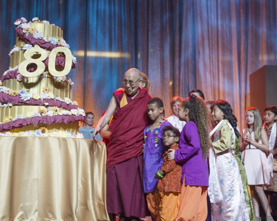 His Holiness the Dalai Lama admiring the large birthday cake presented to him during celebrations honoring his 80th birthday at the Honda Center in Anaheim, California, USA on July 5, 2015. Photo/Tenzin Choejor/OHHDL via dalailama.com.