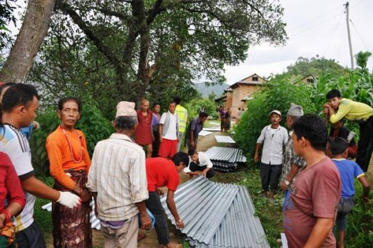 The Namgyal Rinpoche Foundation offering bundles of zinc sheets to Bhanjyang and Phedeghau villages in the Kavre District, Nepal. Photo courtesy of Namgyal Rinpoche Foundation Facebook page.