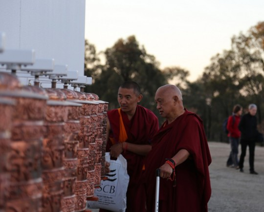 Lama Zopa Rinpoche turning the prayer wheels outside the Great Stupa at dusk, Australia, September 12, 2014. Photo by Ven. Thubten Kunsang