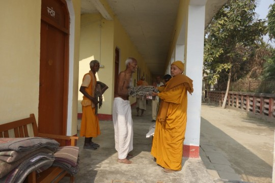 A Buddhist monk offers a blanket to a resident at a home for the elderly and destitute, Kushinagar, India, January 2016. Photo courtesy of Maitreya Buddha Project Kushinagar.