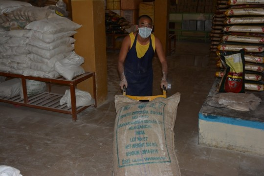 A monk from the Sera Je Food Fund Kitchen helps with flour needed for bread for 30,000.