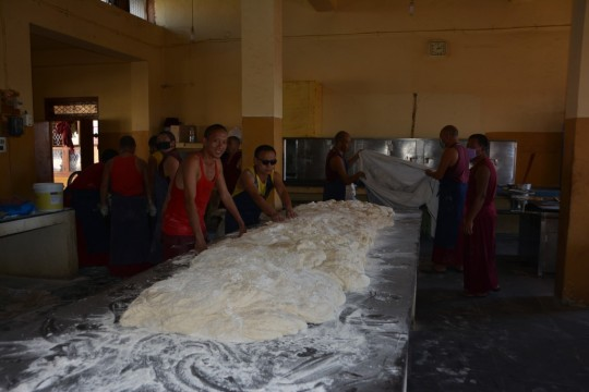 Volunteer monks help kneed the dough required for massive amounts of bread.