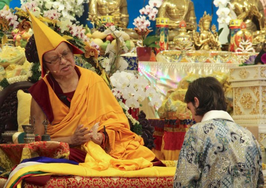 Lama Zopa Rinpoche and Tenzin Osel Hita at long life puja at Amitabha Buddhist Centre, Singapore, March 13, 2016. Rinpoche is offering Osel a gift of a crystal Buddha statue.