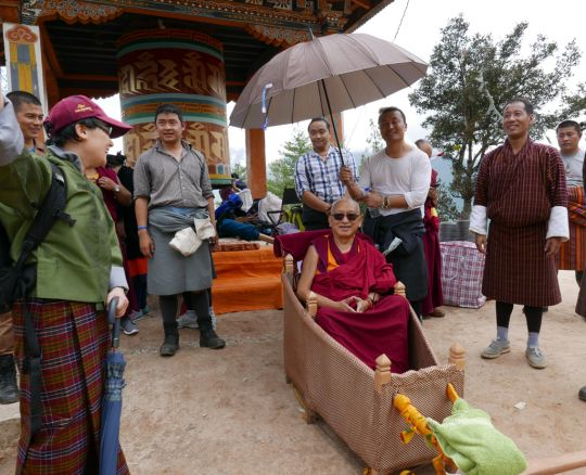 Lama Zopa Rinpoche and entourage stop for a short break two-thirds of the way along the trail to Tiger's Nest Monastery. It had just started to rain, Bhutan, May 2016. Photo by Ven. Roger Kunsang.