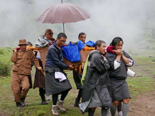 Lama Zopa Rinpoche arrives back at the trailhead after three hours in the rain with the assistance of generous volunteers, Tiger's Nest, Bhutan, May 2016. Photo by Ven. Roger Kunsang.
