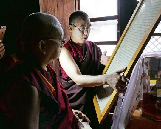 Inside Jangtsa Dumtseg Lhakhang, KhenpoPhuntsokTashishows Lama Zopa Rinpoche sacred objects, Bhutan, May 2016. Photo by Ven. Roger Kunsang.