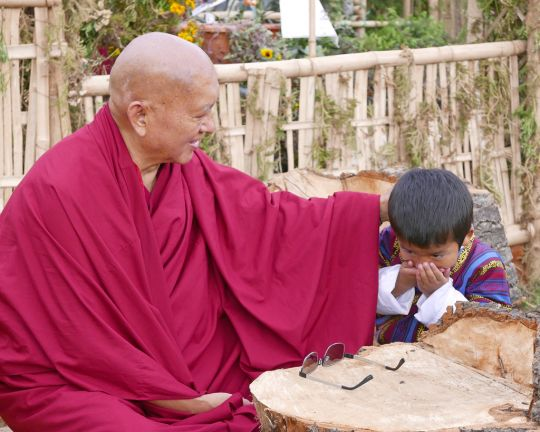 Lama Zopa Rinpoche and a young boy covering his mouth in respect, Paro, Bhutan, June 2016. Photo by Ven. Roger Kunsang.