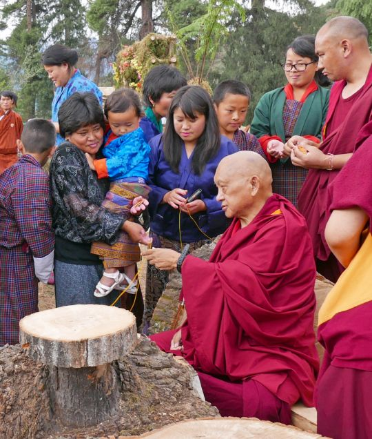 Lama Zopa Rinpoche handing out blessing cords at a flower show, Paro, Bhutan, June 2016. Photo by Ven. Roger Kunsang.