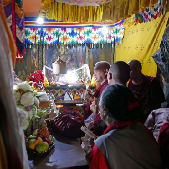 Lama Zopa Rinopche doing prayers in front of a Guru Rinpoche statue that is said to have spoke, inside the tiny gompa at the holy site of Guru Rinpoche's body, Paro, Bhutan, June 2016. Photo by Ven. Roger Kunsang.