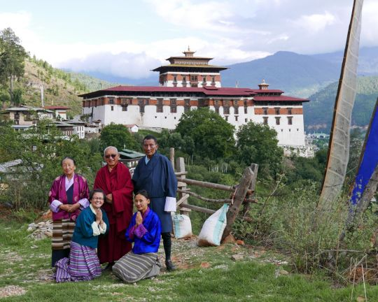 Lama Zopa Rinpoche with a  Bhutanese family in front of Rinpung Dzong, Bhutan, June 2016. Photo by Ven. Roger Kunsang. The mother of the family is Tibetan and took care of Rinpoche many years ago when he was a boy studying in Tibet.
