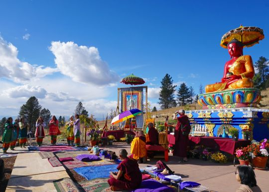 Rinpoche and festival attendees watch the Tara dance offering