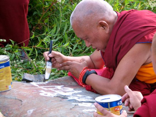 Lama Zopa Rinpoche painting mantras onto rock, Manali, India, July 2013. Photo by Maya.