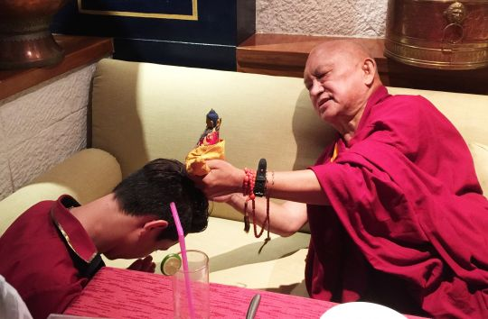 Lama Zopa Rinpoche blesses a waiter in a restaurant in Thailand, June 2016. Photo by Ven. Holly Ansett.