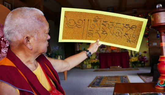 "Lama Zopa Rinpoche examines a ""Just by Seeing"" mantra he has written out, Washington, USA, October 2016."