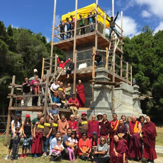 Land of Medicine Buddha community filing the ninth and final structural chamber of the Mahabodhi stupa.