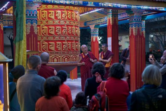 Lama Zopa Rinpoche at the Root Institute next to the large prayer wheel. Photo by Bill Kane.