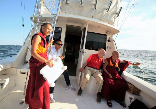Lama Zopa Rinpoche pours blessed water into the Atlantic Ocean off New York, USA, August 2016. Ven. Sangpo is holding a laminated Namgyalma mantra in his hand in preparation for putting it into the ocean. Photo by Ven. Lobsang Sherab.