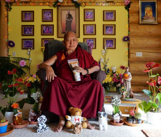 "Lama Zopa Rinpoche surrounded by ""friends"", holding tea offered by Kunsang Yeshe Retreat Centre in Australia. Washington State, USA, November 2016. Photo by Ven. Lobsang Sherab."