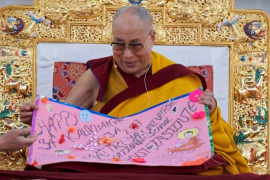 Hi Holiness examining the placard offering best wishes from the children of Maitreya School, Bodhgaya, India, January 2017. Photo by Bill Kane.
